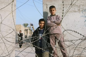 Iraqi children outside razor wire barrier in front of Iskandariyah Police Station, January 2005