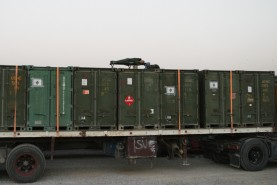 US soldier sleeps on top of shipping containers before during break in convoy north from Kuwait to Iraq, July 2004
